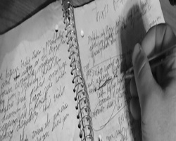 Picture of someone writing in a notebook